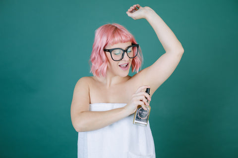 Woman spritzing her pits with Pit Liquor deodorant
