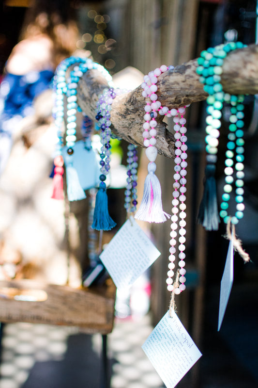 Handcrafted and handmade Malas hanging on display at Legacy Brewing Company. Photograph taken by Rachel Smith Photography.
