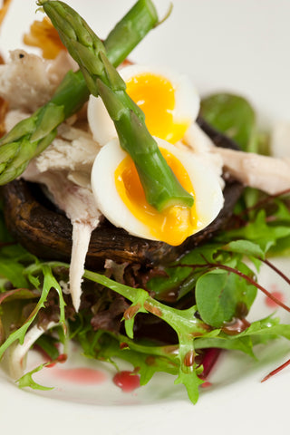 Warm salad of smoked, corn fed, local chicken with asparagus and quails eggs on a field mushroom