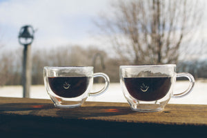 two double wall Lunae espresso cups against a snowy background
