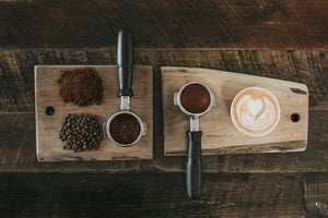 wooden board with whole coffee beans, coffee grounds, two filters and a cup of coffee (showing the process of making coffee)