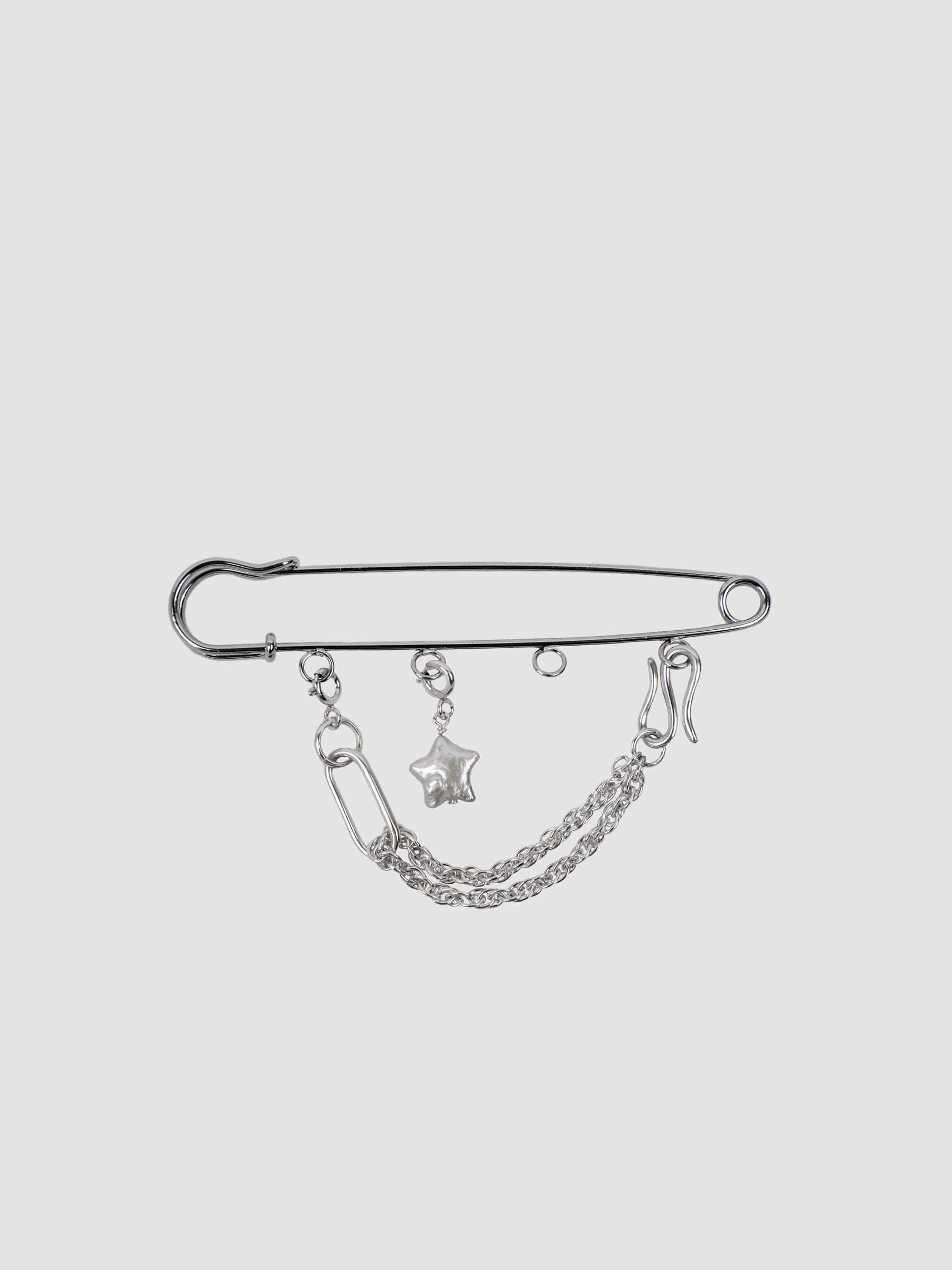 The SONYA LEE x KARA YOO Kilt pin charm. An oversized nickel-plated pin customizable piece for weighing down the top flap of a skirt or for otherwise personalizing blouses, jackets and scarves. Charms can be added and taken away for desired look. Made in Canada.