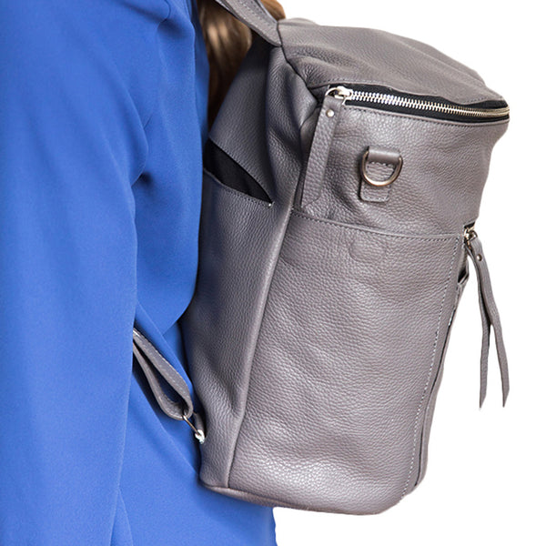 Back view gray backpack. Genuine leather. Girl carrying  backpack on back using shoulder straps.