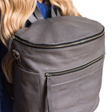 Side view gray backpack. Genuine leather. Girl carrying on back using shoulder straps.