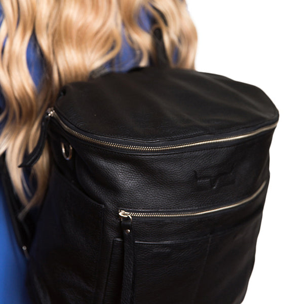 Back  view.  Black backpack. Genuine leather. Girl carrying  backpack on back using shoulder straps.