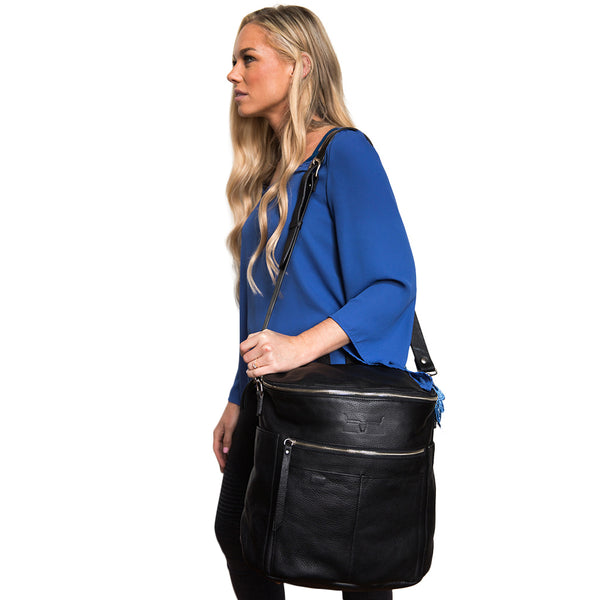Side view of black leather backpack carried on girl's shoulder using strap.
