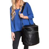 Black genuine leather front view of carried on girl's shoulder using strap.