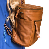 Side view light brown backpack. Genuine leather. Girl carrying on back using shoulder straps.