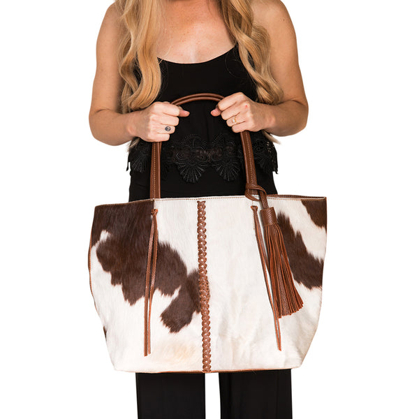 Front view. Woman holding brown and white speckled cow hide braid bag using handles. Braided brown leather strip down middle of bag. Removable brown leather tassel.