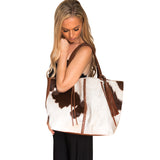 Side view of brown and white speckled cow hide braid bag with shoulder strap.  Woman carrying over shoulder. Braided brown leather strip down middle of bag. Removable brown leather tassel.