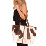 Side view of brown and white speckled cow hide braid bag with woman carrying by handles at elbow. Braided light brown leather strip down middle of bag. Removable brown leather tassel.