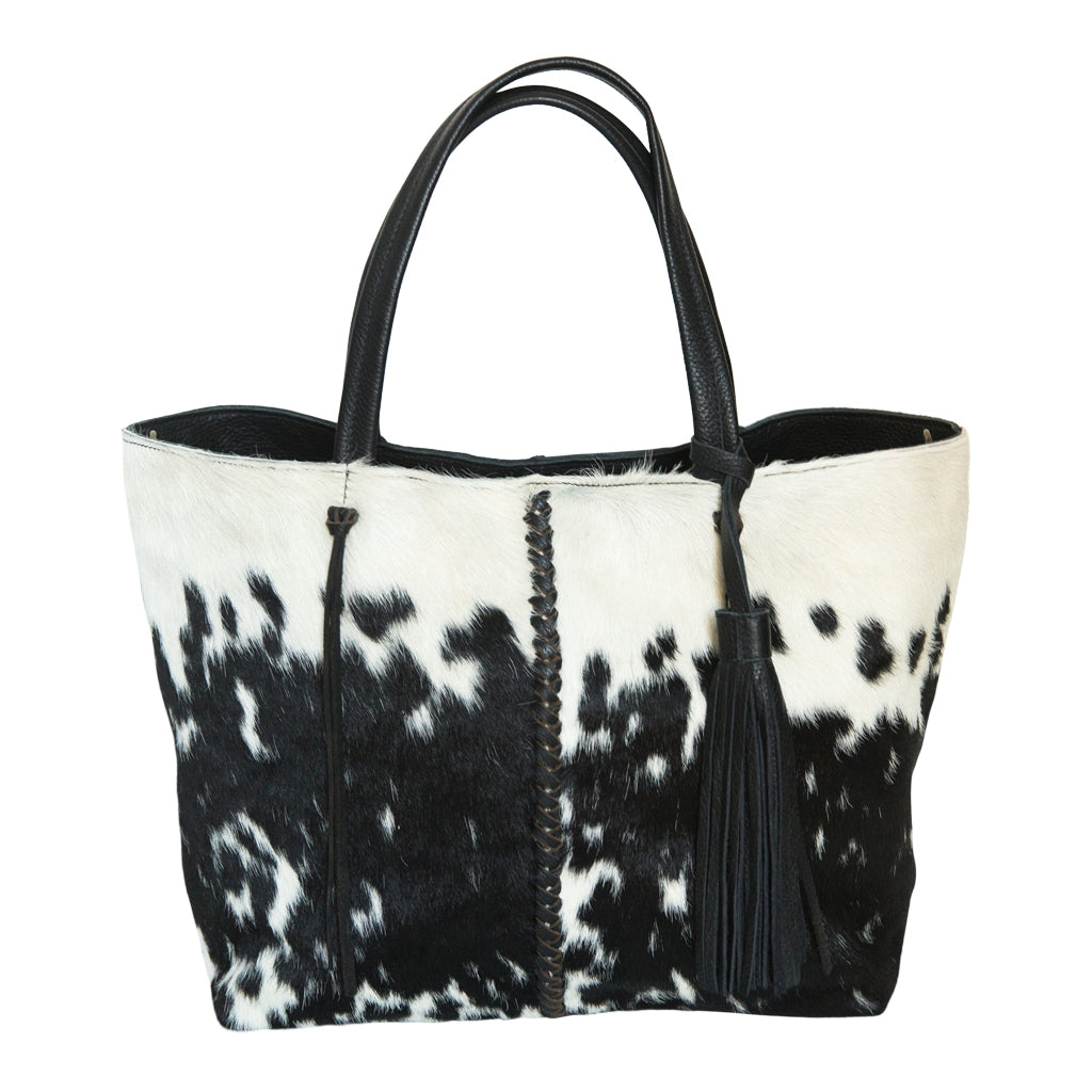 Speckled black and white cow hide  handbag.  Front view.  Braided black leather strip down middle of bag. Handles. Removable black leather tassel.