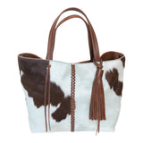 Speckled brown and white cowhide  handbag.  Front view.  Braided brown leather strip down middle of bag. Handles. Removable brown leather tassel.
