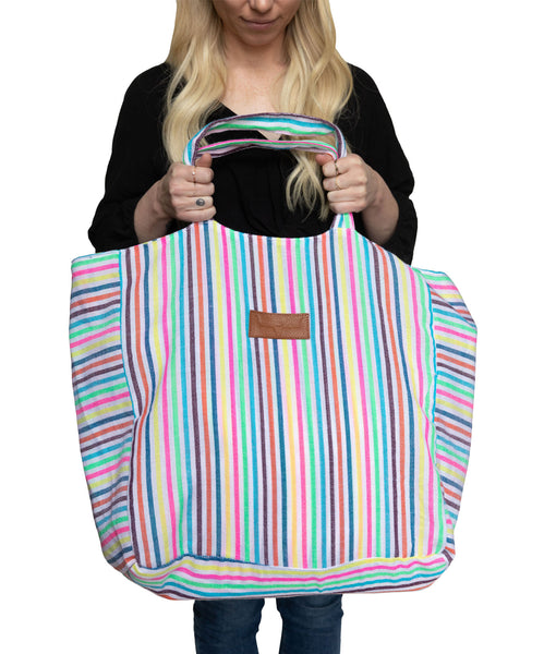 Front view striped beach bag with handles at top.  Multi colored stripes. Girl holding beach bag in  front of body to show size.  Length is elbow to knee.  Width about three inches from  elbow to elbow.