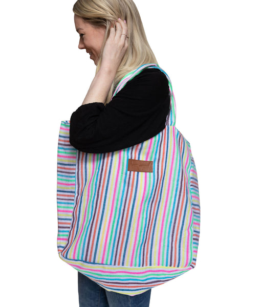 Side view striped beach bag. Multi colored stripes. Girl carrying beach bag over shoulder..olding beach bag on side of body to show size.  Length is elbow to knee.  Width about three inches from  elbow to elbow.