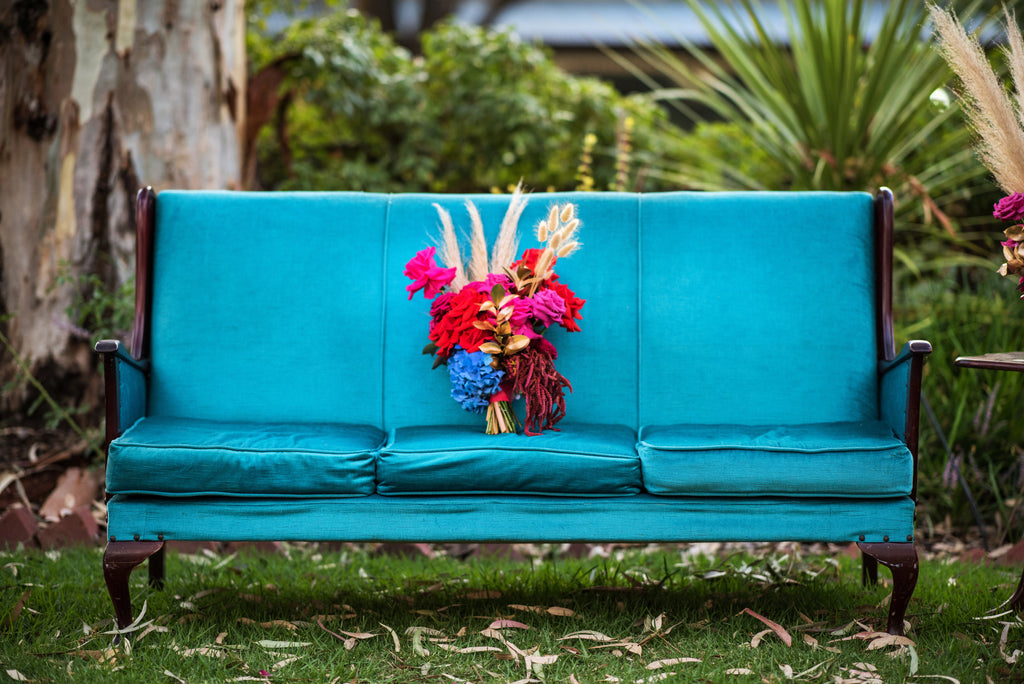 a blue chair with a bunch of pink flowers sitting on it