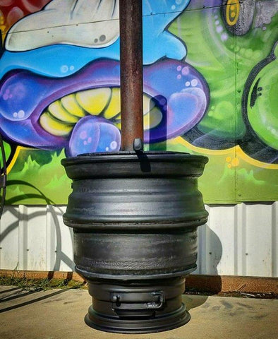 a black metal potbelly stove sits in front of a graffitied wall