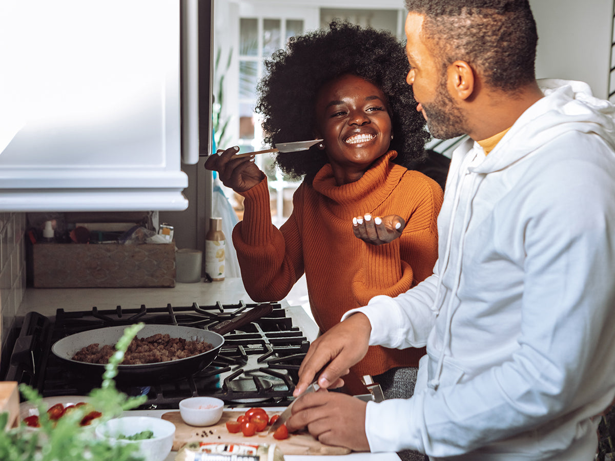 An image of a couple cooking together.