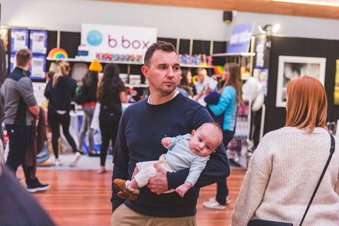 Image of father and child in front of B.Box and Baby Box stand at the Wellington Baby Expo
