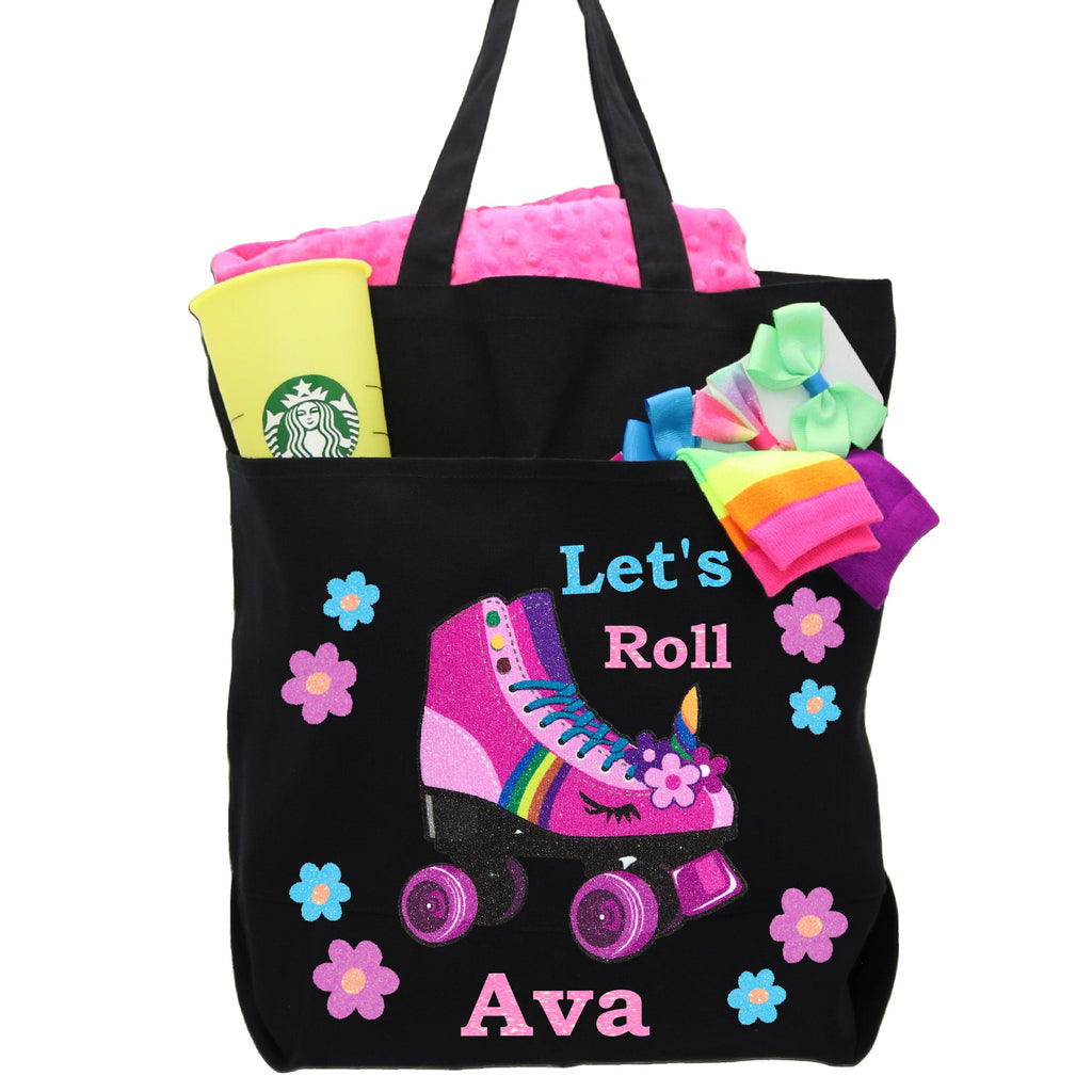 Black Tote bag with pink roller skate and flowers, bag filled with starbucks cup, socks and blanket