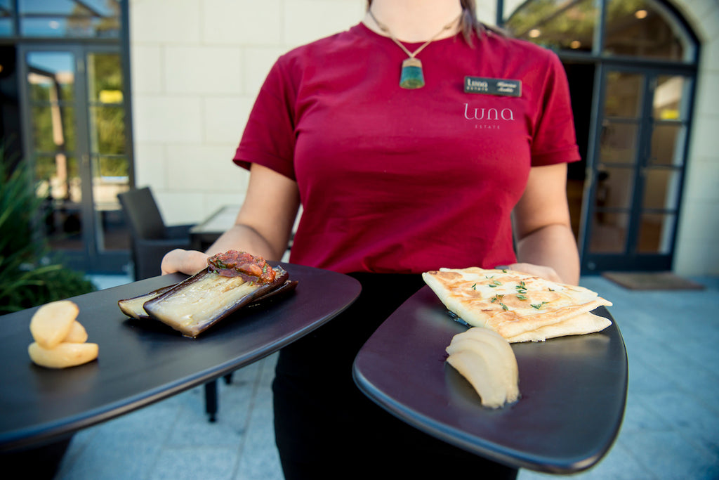 Waitress at Luna Kitchen bringing out selection of food