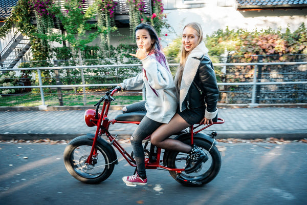 Girls on cool electric moped UNI Moke