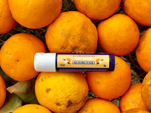 FATCO Fat Stick orange and vanilla laying on top of a giant pile of fresh oranges