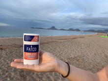Image of a hand holding FATCO Stank Stop natural deodorant, grapefruit & ginger
