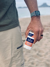 Image of a man on a beach, holding FATCO Stank Stop natural deodorant, grapefruit & ginger