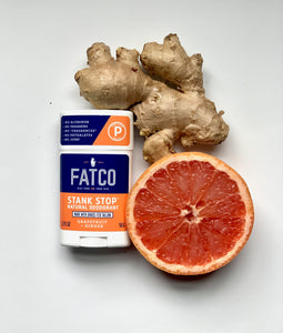 Image showing FATCO Stank Stop natural deodorant, grapefruit & ginger next to a piece of ginger and a cut grapefruit