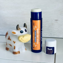 opened FATCO unscented baby fat stick all purpose moisturizing stick standing up next to a toy cow