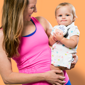 smiling Mother and her baby, with the baby holding a jar of FATCO Baby Butta nourishing tallow balm against an orange background