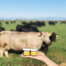 FATCO Calming Body Butta 2 oz jar alongside a FATCO Invigorating Body Butta Tallow balm paleo skincare lotion 2 oz jar with grass-fed cows in the background