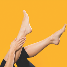 Woman applying FATCO Body Butta Tallow Balm Paleo skincare lotion to her feet and legs against a yellow background