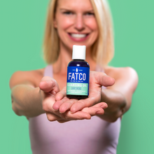 a smiling Woman holding a bottle of FATCO cleansing oil face wash with outstretched arms against a green background