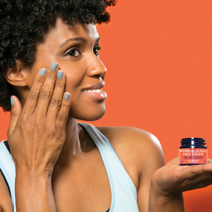 Young black african american woman applies Myrrhaculous Face Cream to her face skin against a red background