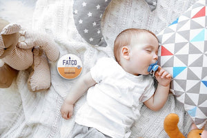 small Baby sleeping in a crib, with a jar of FATCO Baby Butta nourishing tallow balm lying next to him