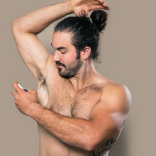 A young and muscular man with a man bun and no shirt topless applying pit spritz deodorizing spray to his armpit underarm against a gray background