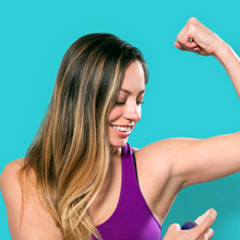 Female woman in a purple tank top spraying FATCO Pit Spritz spray onto her underarms armpits while flexing her muscle and smiling against an aqua background