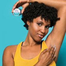 african american black woman applying stank stop natural deodorant paleo to her armpit underarm with her arm draped over her head against an aqua background