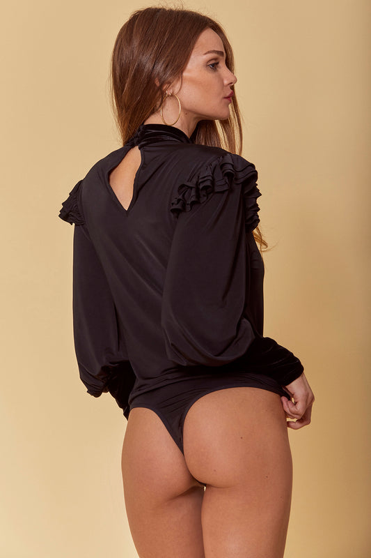 Slinky jersey bodysuit featuring a one piece fitted design with thong bottom with velvet contrast, keyhole front and back cutouts, ruffled accent along bodice and shoulders and long, bubble Victorian sleeves in black.