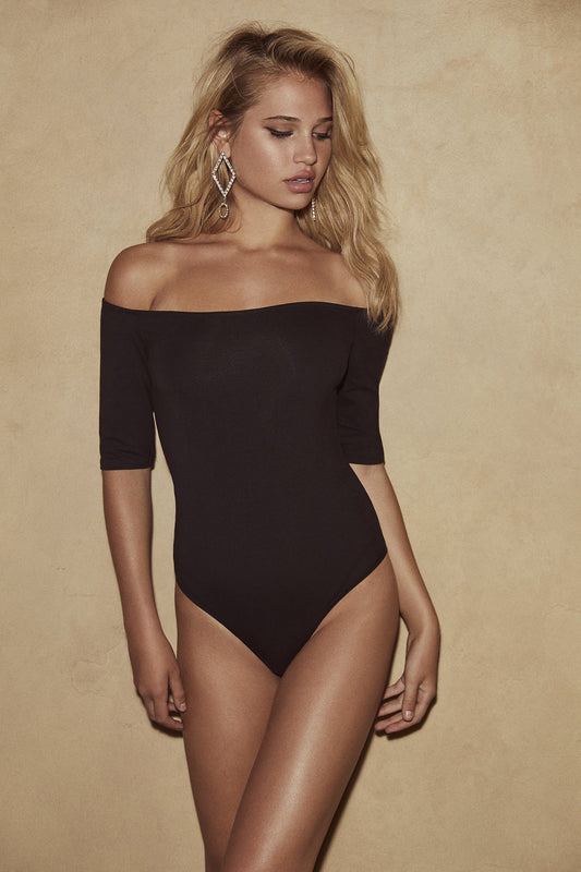 A fitted spandex bodysuit with one piece design, thong bottom and off-the-shoulder fit in black.