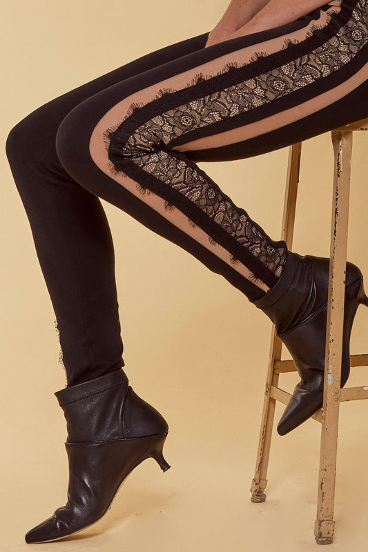 A ponte legging style pant with a fitted mid-rise, lace edge trim, power mesh panels and hidden back zipper in black.