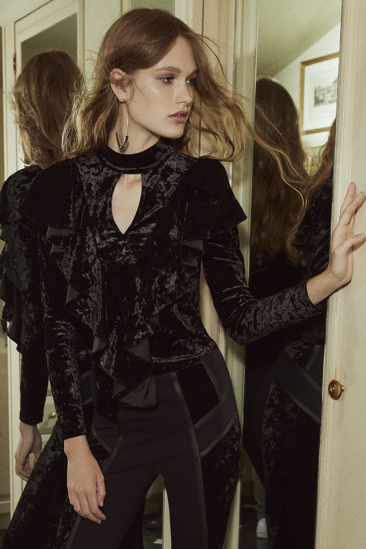 Crushed velvet statement top with long sleeves, keyhole front and back cutouts and ruffled accent along bodice and shoulders in black.