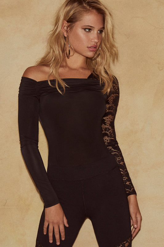 Jersey bodysuit featuring a lace overlay, one piece design, thong bottom and off-the-shoulder fit in black.