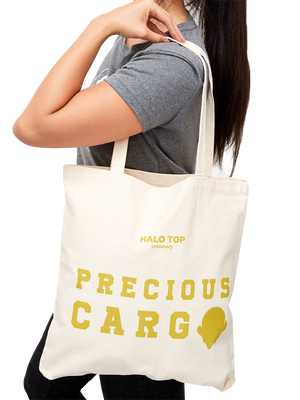 Canvas tote bag with precious cargo text in gold on a model