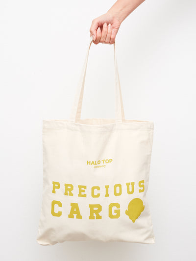 Hand holding canvas tote bag with precious cargo text in gold