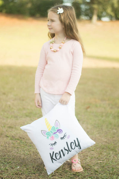 Little girl holding unicorn pillow with personalized name Kensley