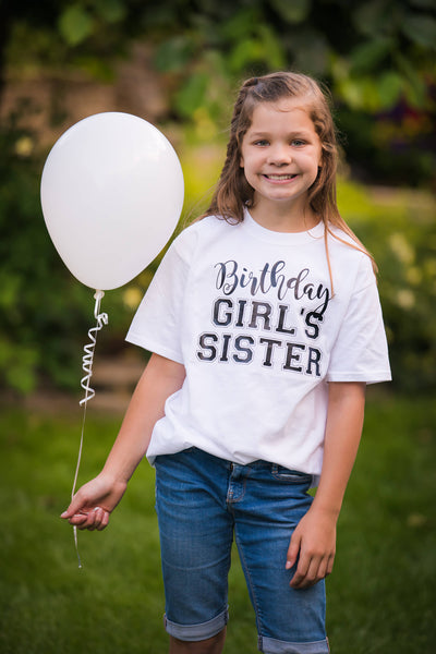 birthday girl's sister wearing white t-shirt and holding a white balloon