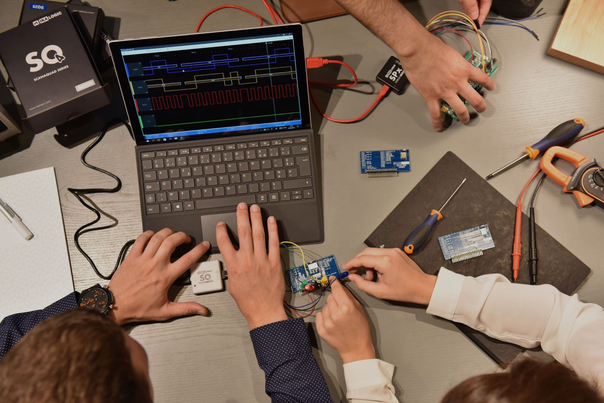 Electronic Engineers working with logic analyzers, signal generator. Serial communication packets are displayed and analyzed on ScanaStudio software